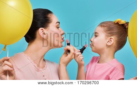 Funny family on a background of bright blue wall. Mother and her child girl are doing your makeup and having fun. Mom and daughter wear lipstick. Yellow, pink and turquoise colors.
