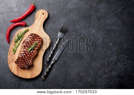 Grilled beef steak on cutting board over stone table. Top view with copy space