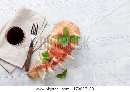 Fresh melon with prosciutto and mint. Antipasti and red wine. Top view on wooden table with copy space