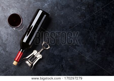 Red wine glass and bottle on stone background. Top view with copy space