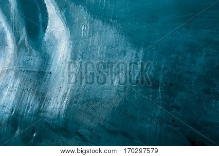 Entrance exit path of a glacier tunnel with solid ice walls and ceiling illuminated blue by sunlight through the ice