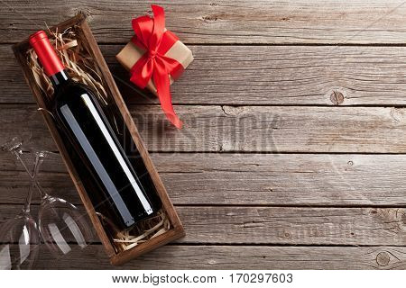 Valentines day greeting card. Red wine, gift box and glasses on wooden table. Top view with space for your greetings