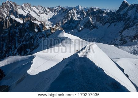 Climber ascending final stretch on arete ridge leading up to Aiguille du Midi in early winter sunny conditions