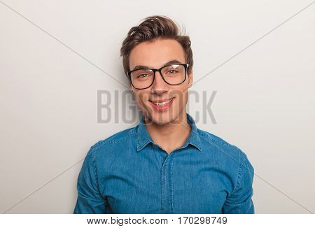 closeup picture of a young man wearing glasses and smiles to the camera , studio picture