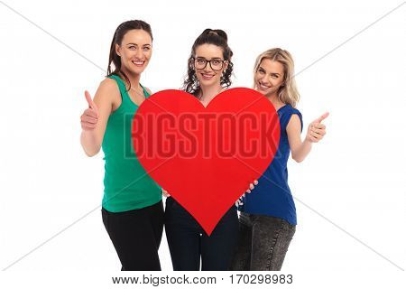 young happy women holding a big heart and make the ok thumbs up hand sign on white studio background