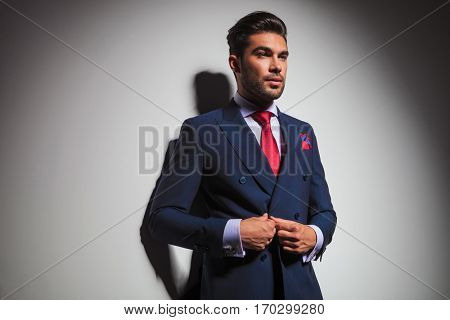 side view of a gentleman buttoning his suit and looks away from the camera on grey wall