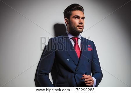 side view of an elegant man in suit and tie thinking and looking up , studio picture
