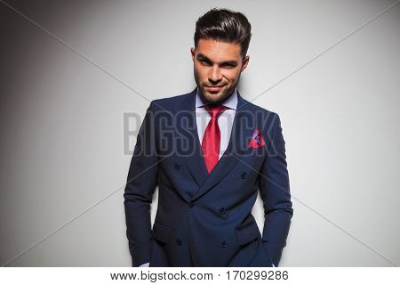 arrogant smiling business man with hands in pockets leaning against grey studio wall
