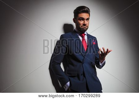 confused elegant man gesturing and making an undecided stupid face, leaning on a grey studio wall