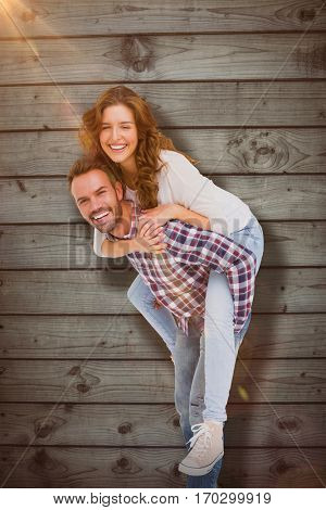 Man giving piggyback ride to woman against close-up of wooden fence