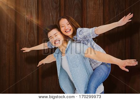 Portrait of happy couple with arms outstretched against wood