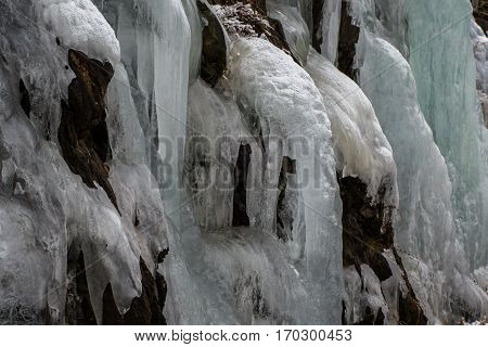 Multiple colour hues in ice fall frozen in flow down hillside with distinct flow shapes