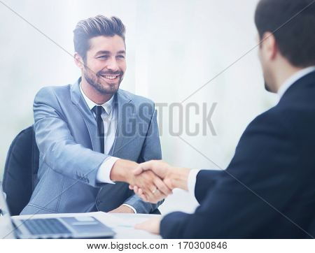 Two business colleagues shaking hands during meeting