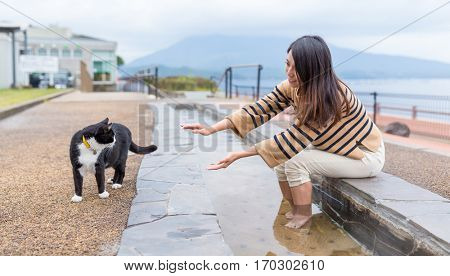 Woman enjoy foot onsen and play with cat