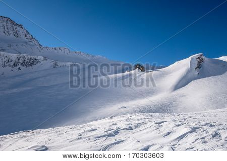 Remote alpine refuge in early winter snow cover without traces of skiers