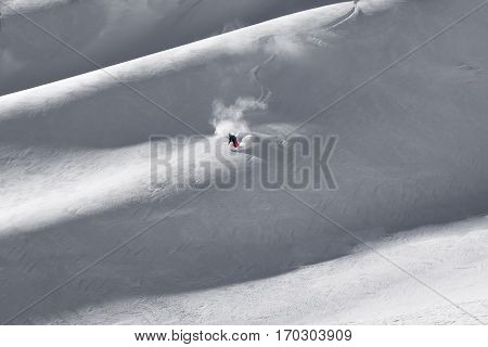Courmayeur Italy - January 16 2017: Fresh first tracks put down by single lone skier coming down mountain ridge spraying new fallen snow in turns