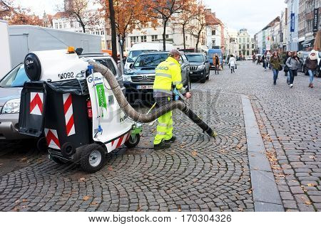 Ghent, Belgium - November 19, 2016: Worker cleans the street with vacuum car in Ghent, Belgium