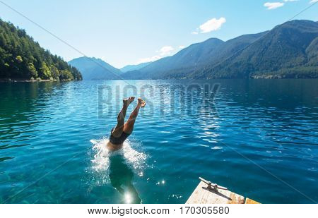 Man jumping in Crescent lake,Olympic National Park,Washington, USA