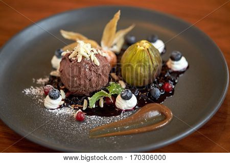 food, new nordic cuisine and sweets concept - close up of chocolate ice cream dessert with blueberry kissel, honey baked fig and greek yoghurt on plate at restaurant
