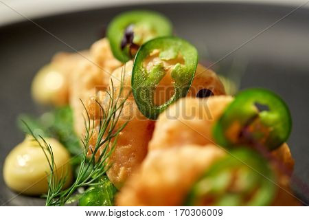 food, new nordic cuisine, culinary and cooking concept - close up of king prawns with jalapeno on plate