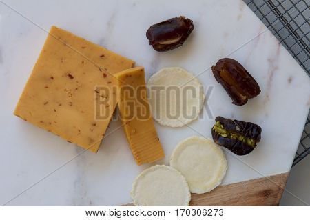 Chipotle spiced cheese on a board with dry savoury biscuits and stuffed dates.