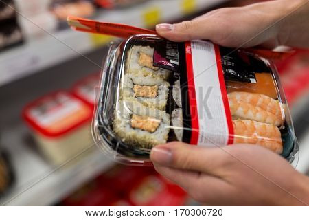 sale, shopping, consumerism and people concept - hands with sushi pack at grocery or supermarket