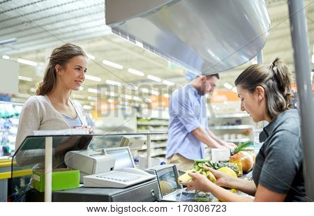 shopping, sale, consumerism and people concept - happy couple buying food at grocery store or supermarket cash register