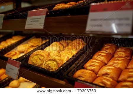 food, baking and sale concept - close up of buns at bakery or grocery store