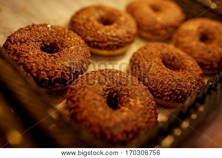 food, baking and sale concept - close up of chocolate donuts at bakery or grocery store