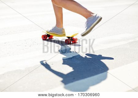 summer, extreme sport and people concept - male legs riding short modern cruiser skateboard along crosswalk