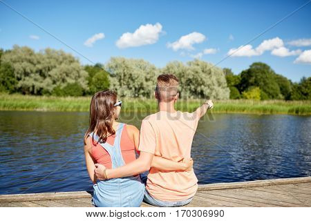 holidays, vacation, love and people concept - happy smiling teenage couple hugging and pointing finger to something on river berth at summer