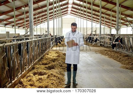 agriculture industry, farming, people and animal husbandry concept - veterinarian or doctor with clipboard and herd of cows in cowshed on dairy farm
