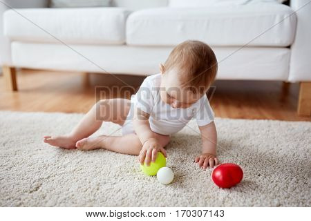 childhood, babyhood and people concept - happy baby playing with balls on floor at home