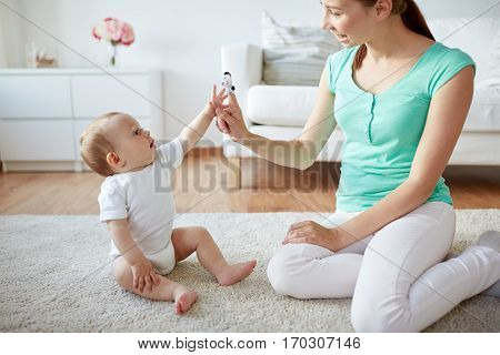 family, children and parenthood concept - happy smiling young mother and baby playing with finger puppet at home