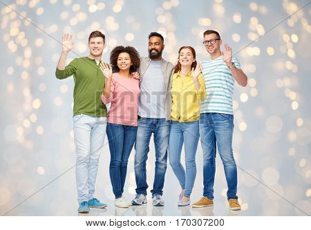 diversity, race, ethnicity and people concept - international group of happy smiling men and women waving hands over holidays lights background