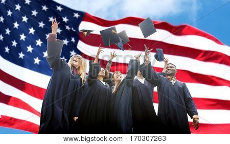 education, graduation and people concept - group of happy international students in bachelor gowns throwing mortarboards up over american flag background