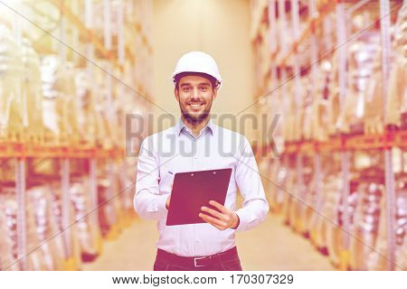 wholesale, logistic, business, export and people concept - happy man or manager with clipboard checking goods at warehouse