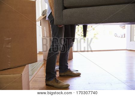 Close Up Of Man Carrying Sofa Into New Home On Moving Day