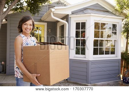 Woman Carrying Box Into New Home On Moving Day