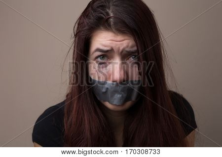 Frightened brunette hostage with tape