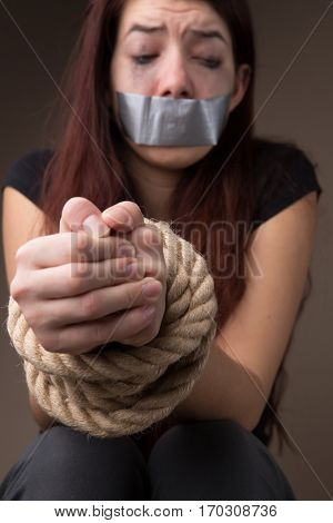 Crying brunette with hands tied
