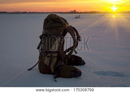 backpack on snow against sunset background