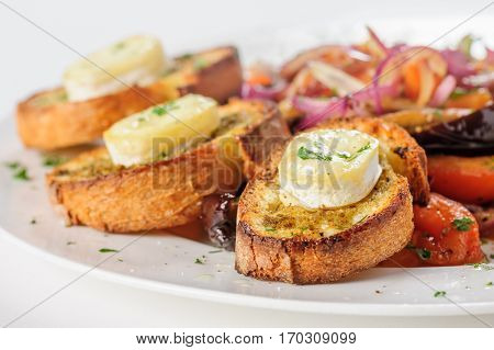 Grilled cheese on bread with salad of tomato, eggplants, red onion and lettuce, selective focus