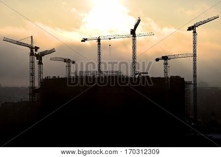 Construction cranes silhouetted against a sunset sky