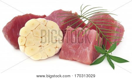 Raw beef with garlic and green herbs over white background