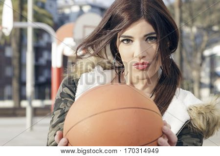 Woman Holding A Basket Ball On A Sports Playground.