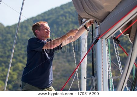 Skipper tightens the ropes on his sailing yacht.