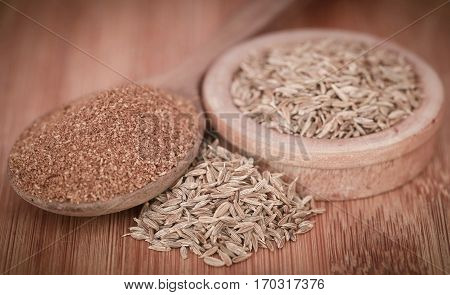 Closeup of crushed cumin with whole ones