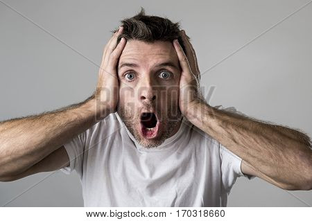 young attractive man astonished and amazed in shock and surprise face expression as paradigm of facial for shock emotion isolated on grey background