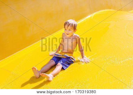 Smiling boy on a waterslide